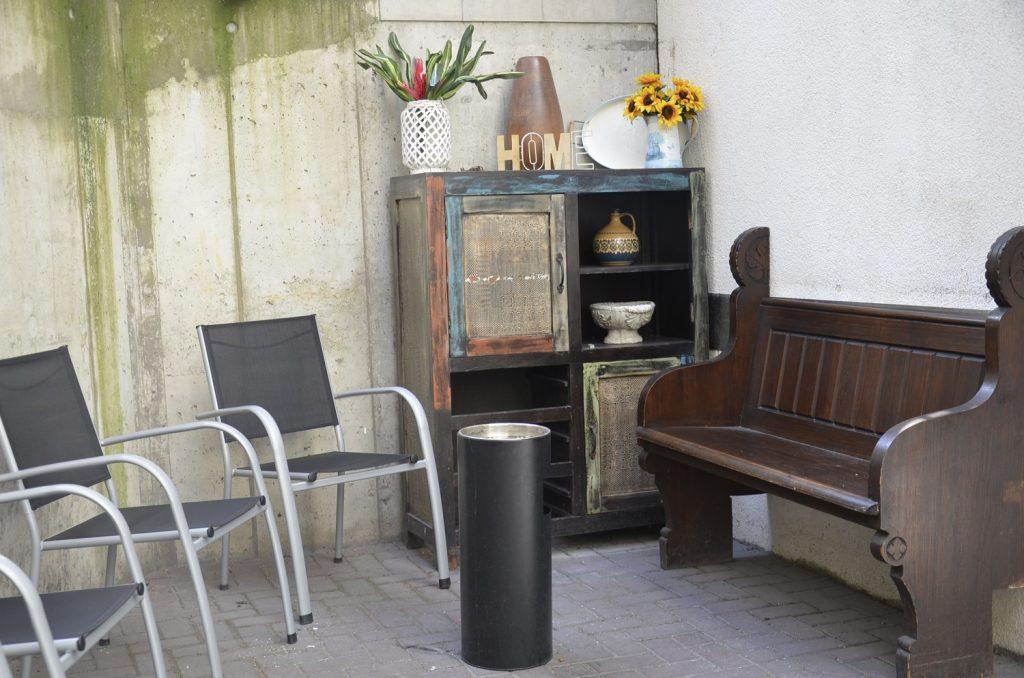 Eine alte Kirchenbank und bequeme Stühle um eine Aschenbechersäule. In der Ecke steht ein alter Küchenschrank. Er ist hübsch bemalt und dekoriert. Unter anderem steht eine Kanne mit Sonnenblumen darauf.