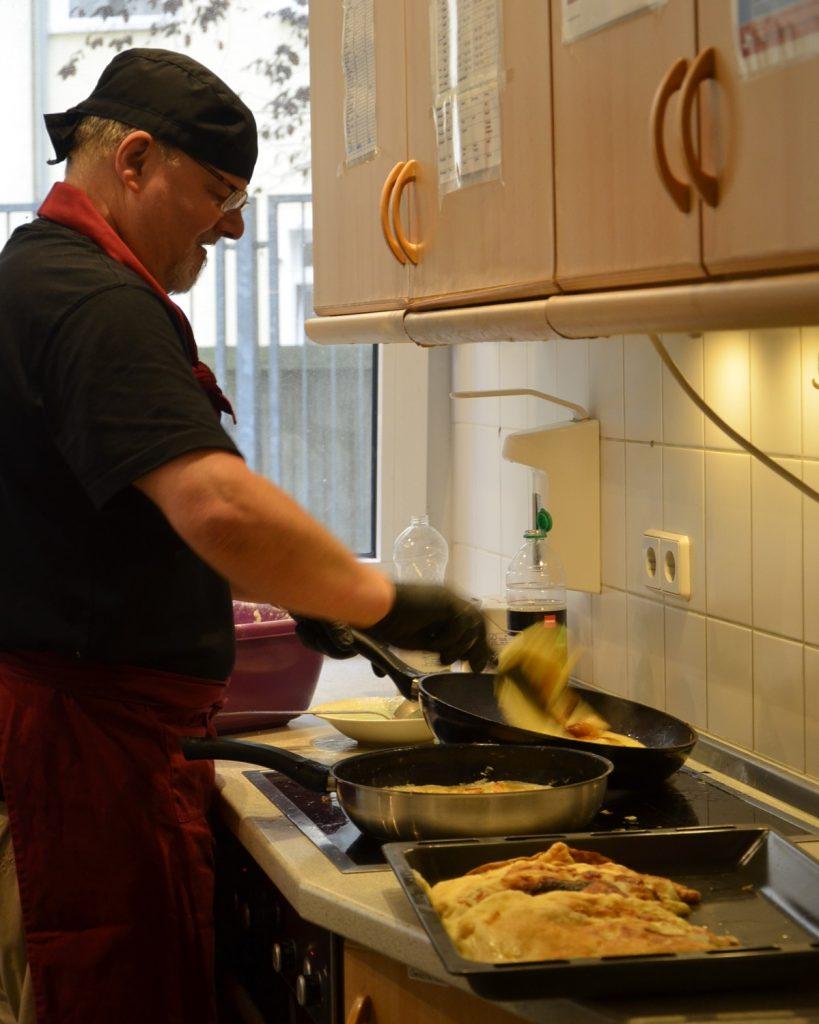 Mike steht in der Küche am Herd. Er wendet etwas in einer Pfanne.