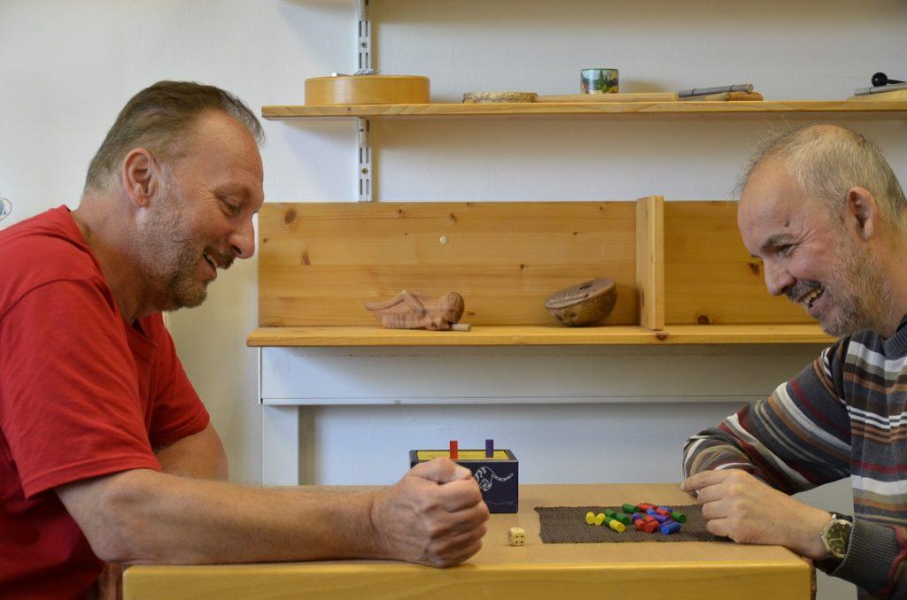 Detlef und Lutz sitzen sich an einem Tisch gegenüber. Vor Lutz liegt ein Stapel kleiner bunter Holzzylinder. Detlef hat gerade gewürfelt. Beide blicken auf den Würfel in der Mitte des Tisches. Beide lächeln.