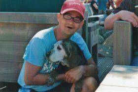 Matti in einem blauen T-Shirt und einer roten Mütze. Er hat einen Hund im Arm.