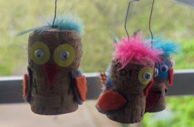 Eulen aus Korken, die Eulen sind beklebt mit bunten Augen und Federn und roten Schnäbeln. Die Eulen gängen am Fenster.